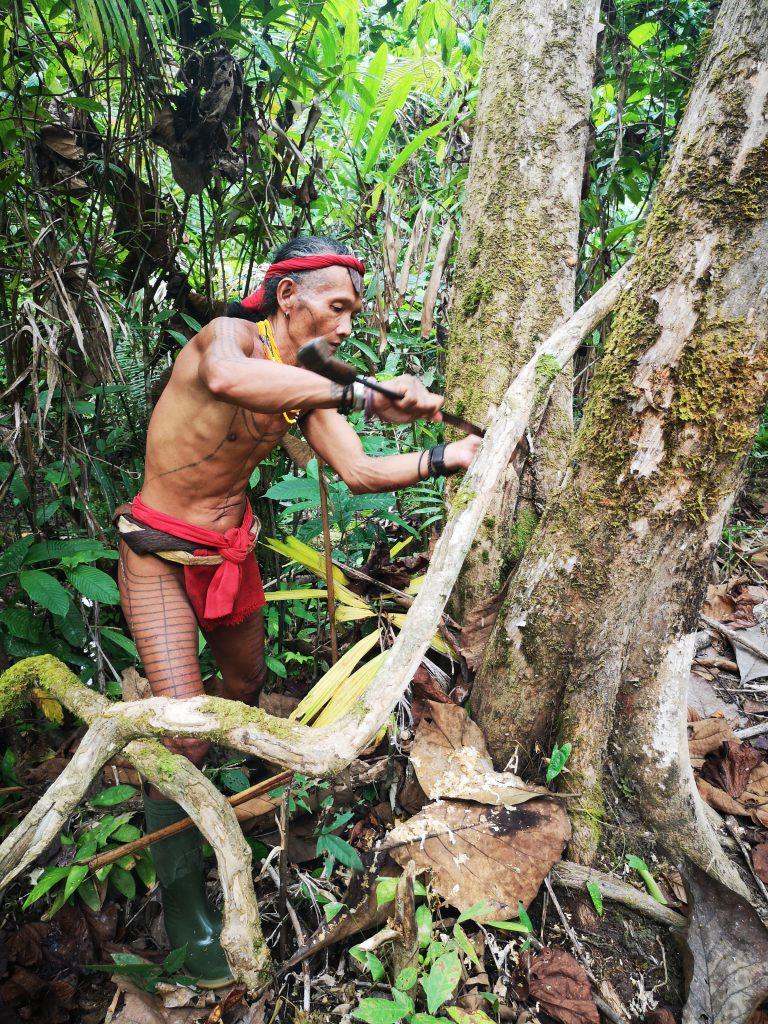 Sjamaan Gresik bezig met vergaren van grondstoffen voor het gif voor op de pijlen